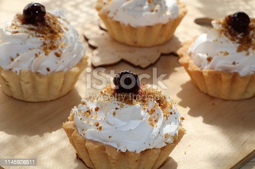 Cupcakes with cream close-up on wooden background. Selective focus. Tasty muffins sprinkled with powdered sugar in paper cups