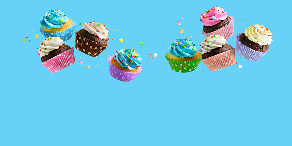 Delicious Cupcakes for party, birthday. Various cupcakes with pink white and blue cream flying over blue background