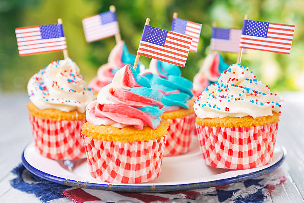 Cupcakes with red-white-and-blue frosting and American flags on outdoor table stock photo