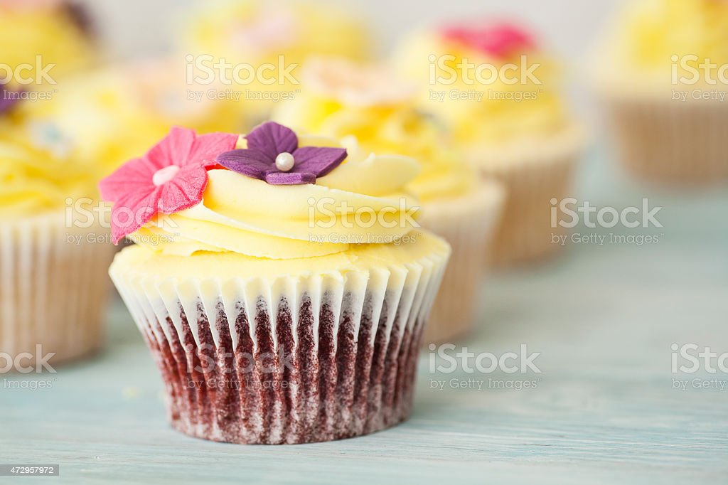 Cupcakes with yellow frosting and flower decoration stock photo cupcakes with yellow frosting and flower decoration royalty free stock photo mightylinksfo