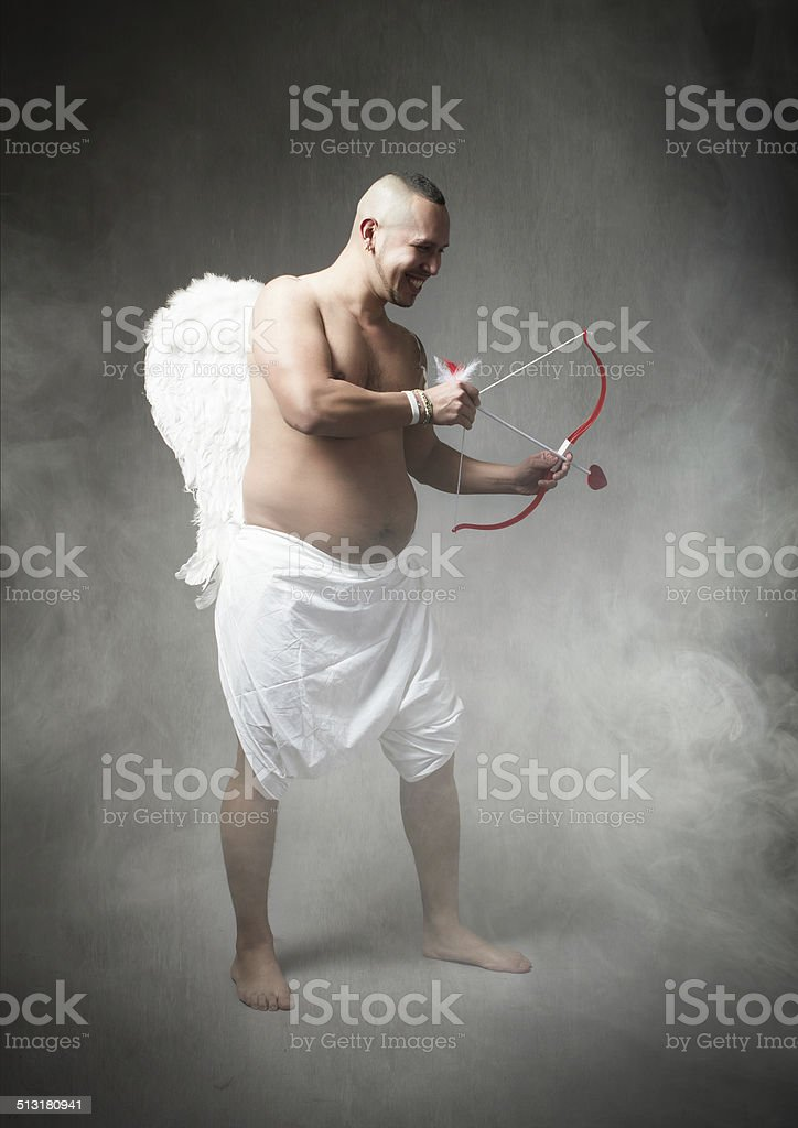Cupid in a cloud of fog ready to hit stock photo