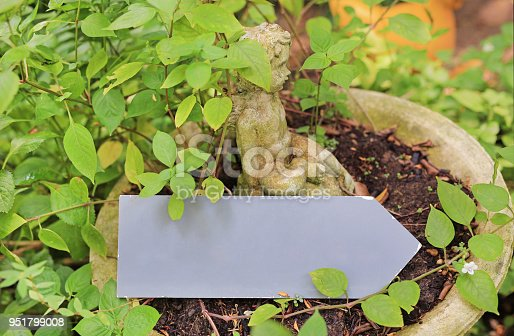 istock Cupid statue and arrow blank label in the garden. 951799008