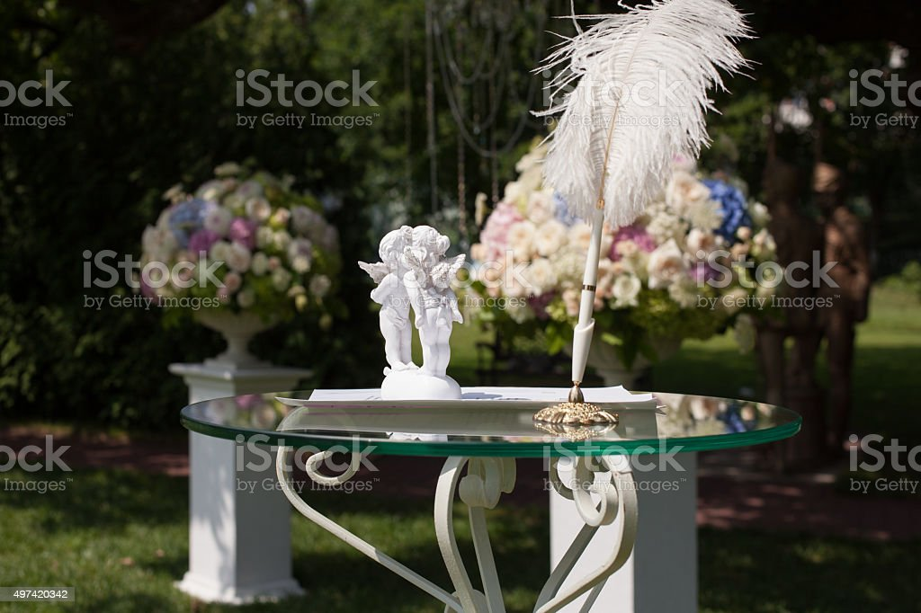 Cupids, pen and certificate on the wedding table stock photo