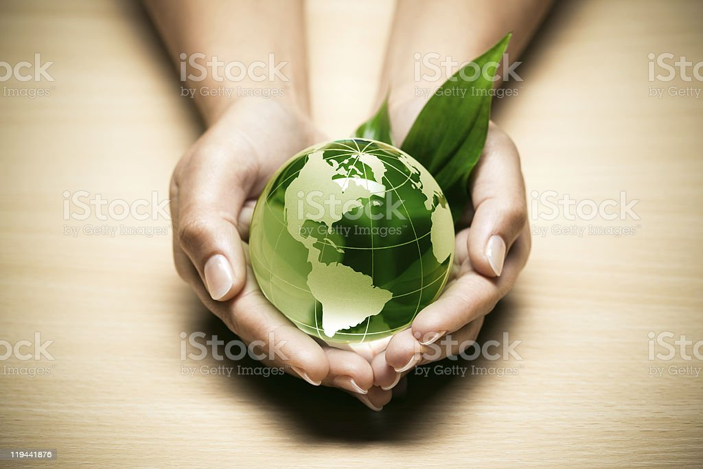 Cupped hands holding a glass globe with some grass royalty-free stock photo
