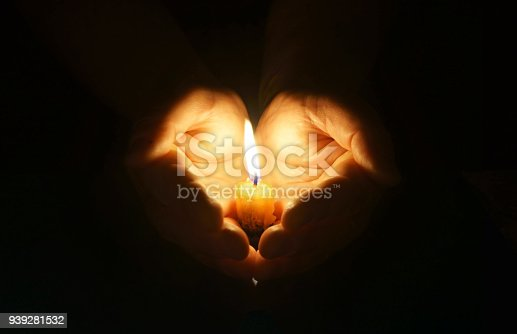 Man hands holding a burning candle in dark.  Cupped hands with burning candle. Gentle protection of fragile fire.