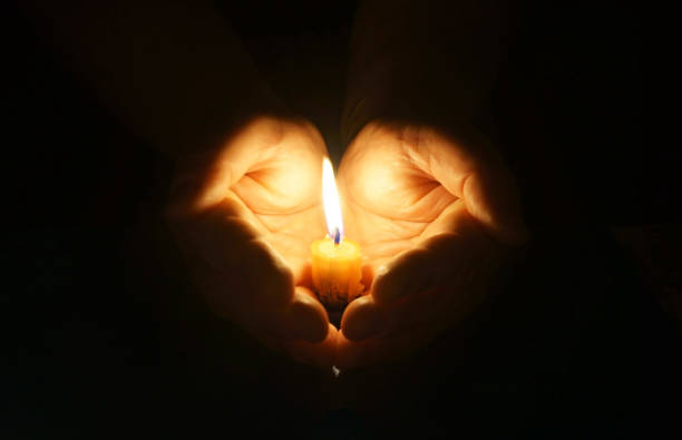 Cupped hands with burning candle. stock photo
