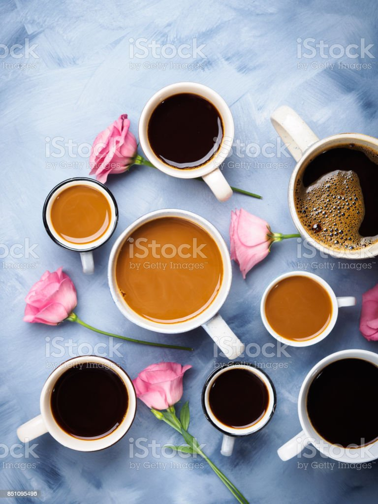 Group of Cups and mugs of coffee and pink flowers on blue background....