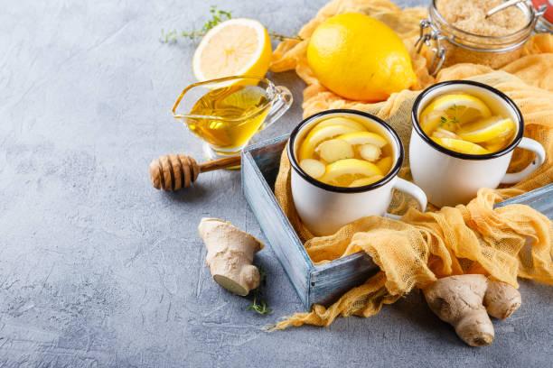 tassen ingwertee mit honig und zitrone - ingwerwasser zubereiten stock-fotos und bilder