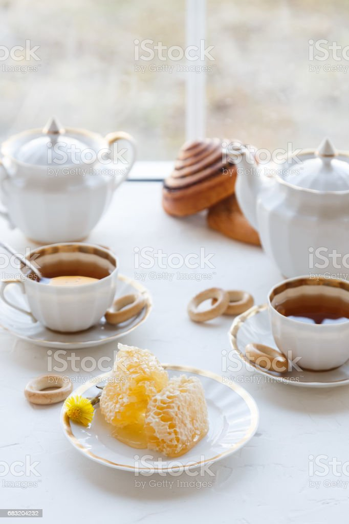 Cups of tea with honey on a plate and teapot, white baackground 免版稅 stock photo