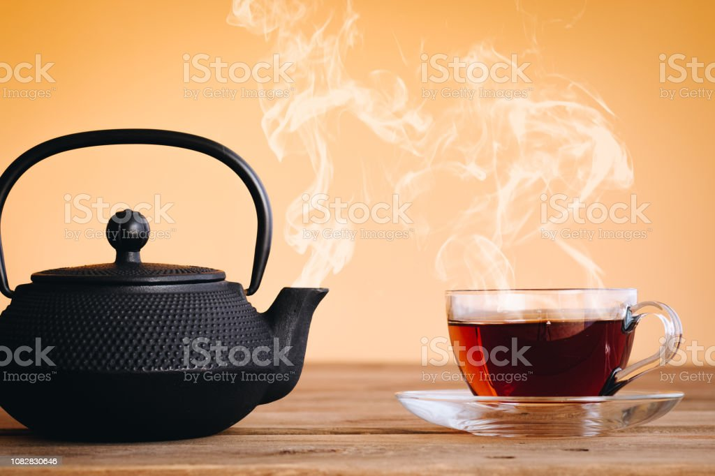 cups of you and iron Kettle hot and steaming, warm tones and space...