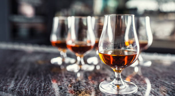 Cups with a cognac rum brandy or whiskey drink on a bar counter in night club. Cups with a cognac rum brandy or whiskey drink on a bar counter in night club. brandy stock pictures, royalty-free photos & images