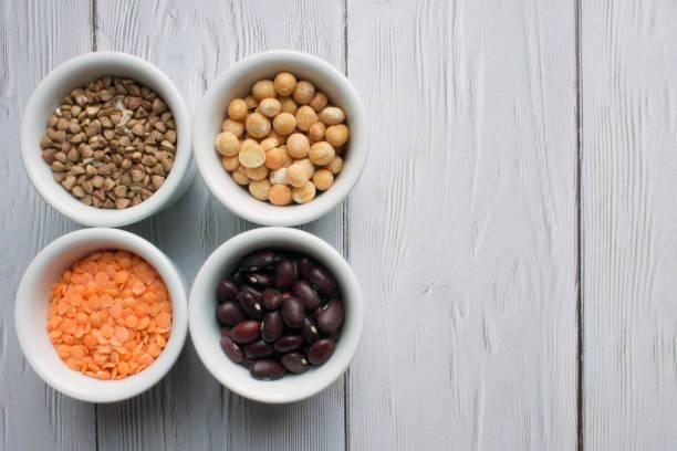 kopjes met granen top view: rode bonen, oranje linzen, boekweit en gele erwten - spoorelement stockfoto's en -beelden