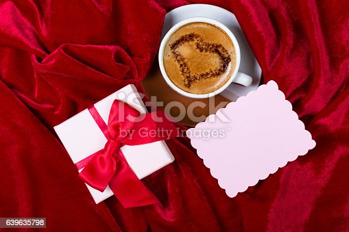 Cups with coffee with drawn heart on the foam, gift box and small paper note for text input on red velvet tablecloth. Top view. Romantic background.