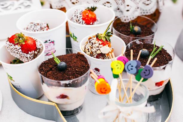 tassen mit kalten desserts stehen auf dem tablett - regenbogen käsekuchen stock-fotos und bilder