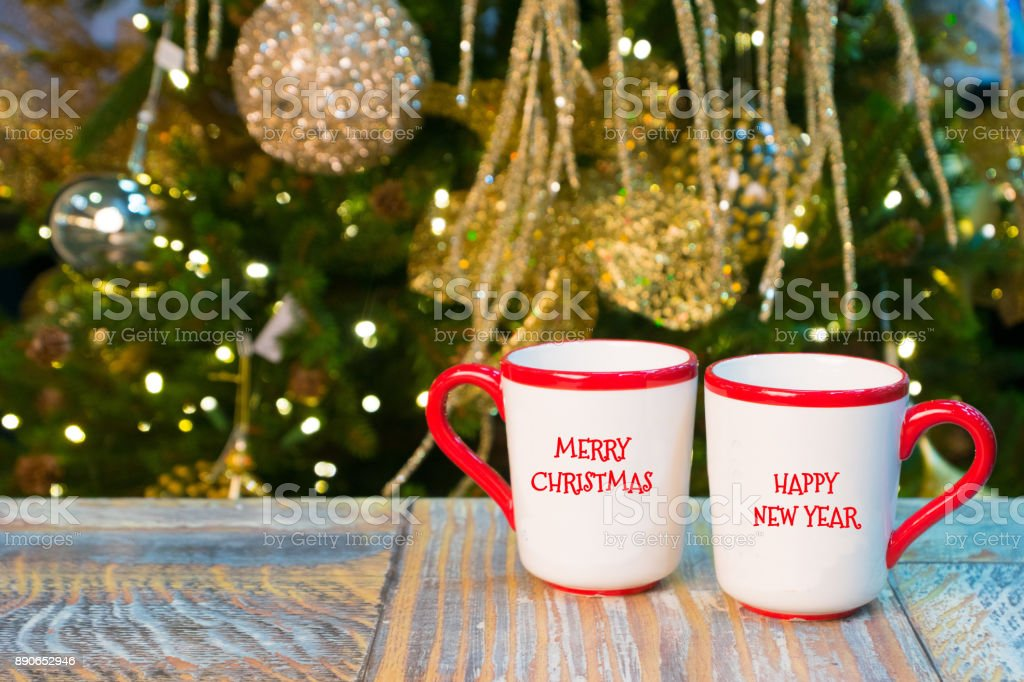 cups with Merry Christmas and Happy New Year greetings on rustic table near xmas decorated tree stock photo