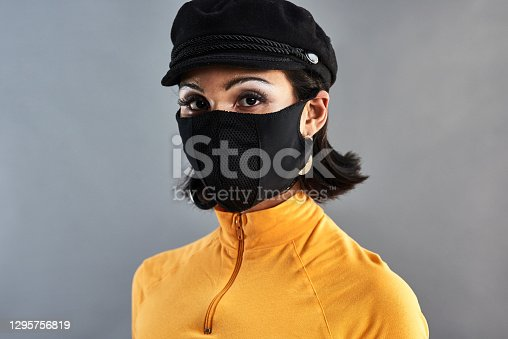 Studio shot of a beautiful young woman wearing a face mask against a grey background