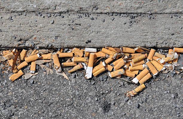 marciapiede pileup sigaretta - cicca sigaretta foto e immagini stock