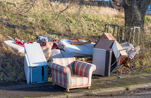 Unwanted household items left on the curbside, including an armchair, matress, fridge, cot and other items.