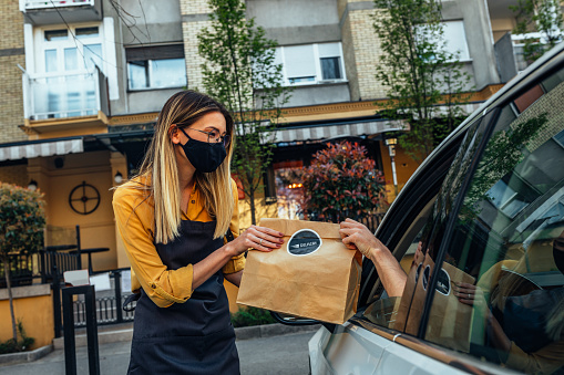 Man picking restaurant food from car at a Curbside pickup