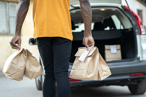 Rear view of a curbside pickup service staff wearing food delivery bags for loading in customer's car