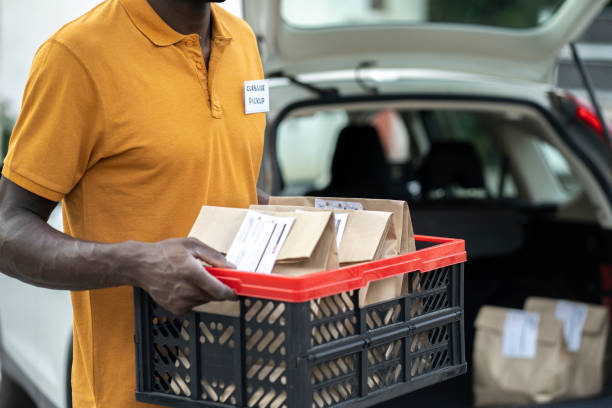 Curbside pickup service staff holding a basket with food delivery Close up of an afro service staff holding a basket with food delivery to load the car waiting for curbside pickup curbsidepickup stock pictures, royalty-free photos & images