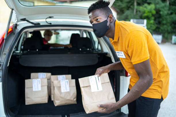 Curbside service staff loading shopping bags for customer while staying in car Young curtsied staff loading shopping bags for a customer due to social distancing curbsidepickup stock pictures, royalty-free photos & images