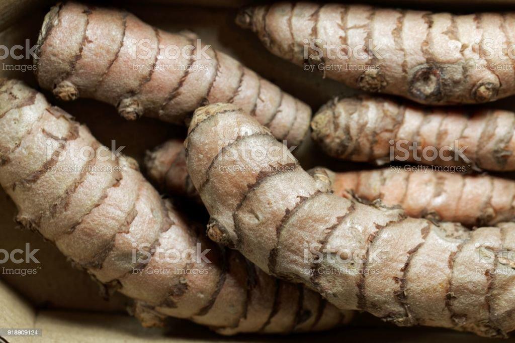 A macro photo of curcuma roots as background.