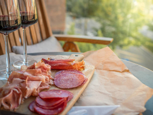 Cured meat, sliced prosciutto and salami. Glasses of red wine on table. Sunlight from side. stock photo