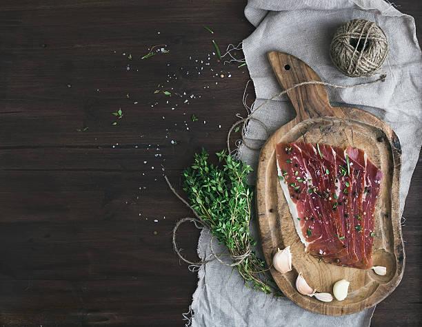 schwein fleisch prosciutto auf rustikalen holz-board - thymian trocknen stock-fotos und bilder