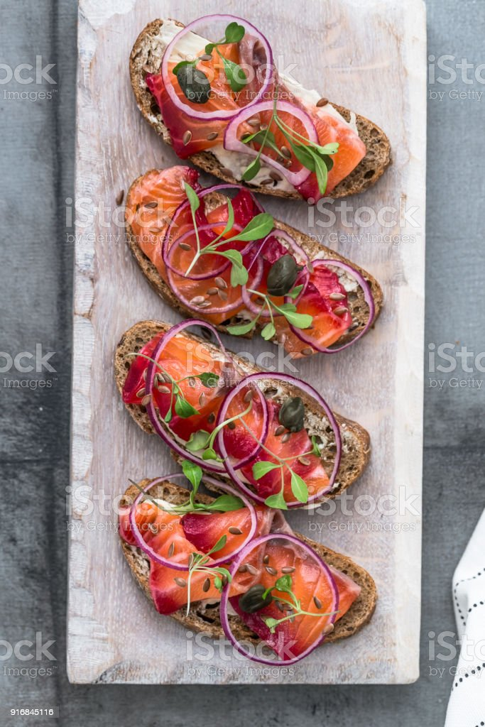 Cured salmon gravlax on a crusty bread stock photo