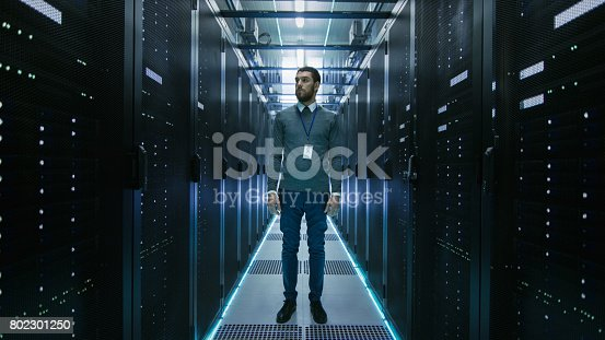 802303672 istock photo Curios IT Engineer Standing in the Middle of a Working Data Center Server Room. 802301250