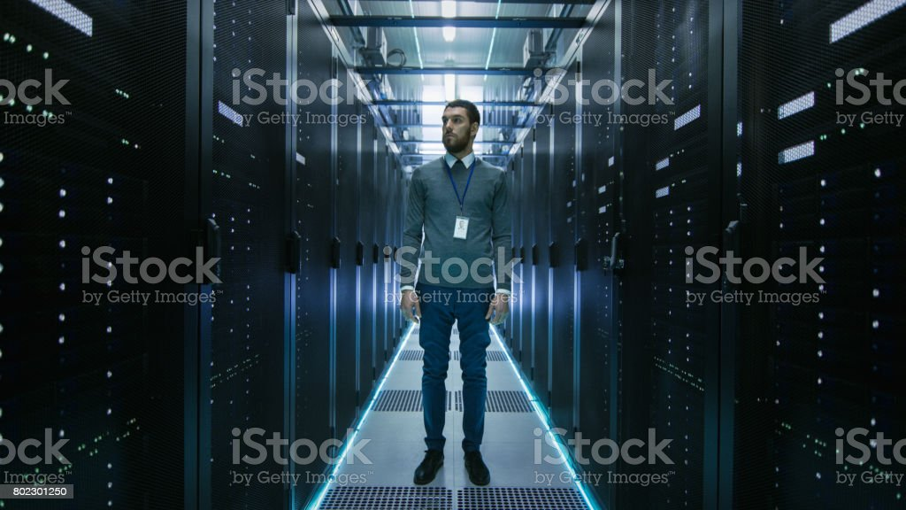 Curios IT Engineer Standing in the Middle of a Working Data Center Server Room. stock photo