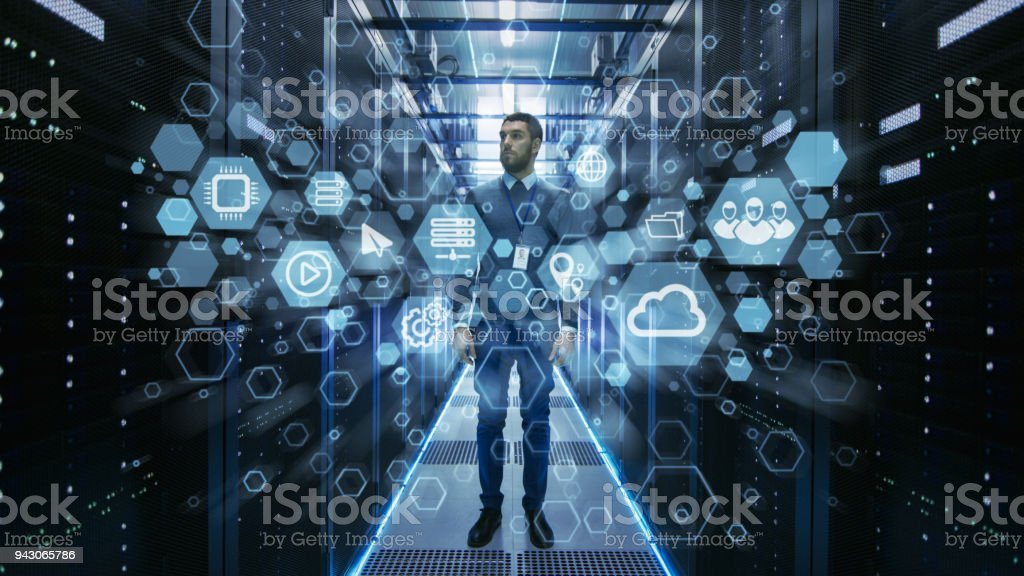 Curios IT Engineer Standing in the Middle of a Working Data Center Server Room. Cloud and Internet Icon Visualization in the Foreground. Curios IT Engineer Standing in the Middle of a Working Data Center Server Room. Cloud and Internet Icon Visualization in the Foreground. Adult Stock Photo