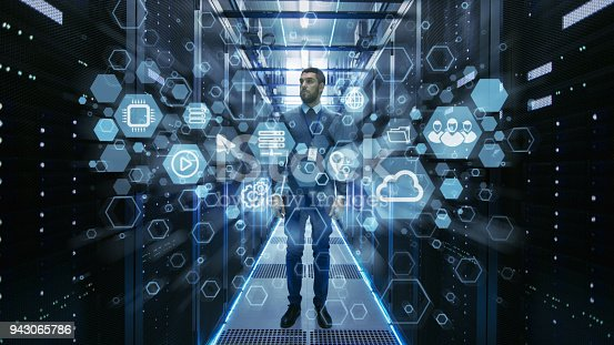802303638istockphoto Curios IT Engineer Standing in the Middle of a Working Data Center Server Room. Cloud and Internet Icon Visualization in the Foreground. 943065786