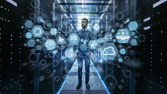 Curios It Engineer Standing In The Middle Of A Working Data Center Server Room Cloud And Internet Icon Visualization In The Foreground Stock Photo - Download Image Now