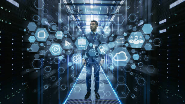 Curios IT Engineer Standing in the Middle of a Working Data Center Server Room. Cloud and Internet Icon Visualization in the Foreground. stock photo