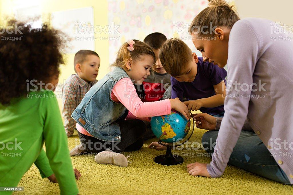 Curios kids examining world globe with their teacher at preschool. stock photo