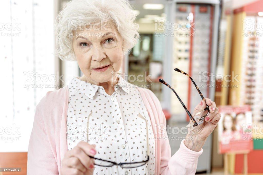 Curios matured woman keeping liked eyewear stock photo