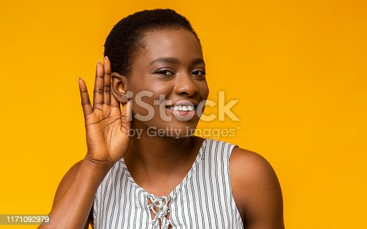 Curious interested african american woman holding hand near ear and trying to hear information, yellow studio background