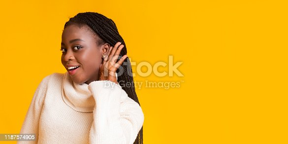istock Curious african-american woman holding hand near ear 1187574905