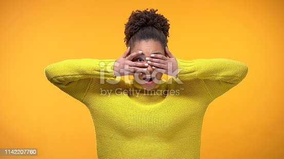 istock Curious afro-american teenager peeping through fingers, interesting situation 1142207760
