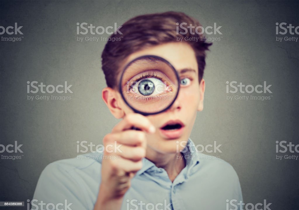 Curious amazed young man looking through a magnifying glass stock photo