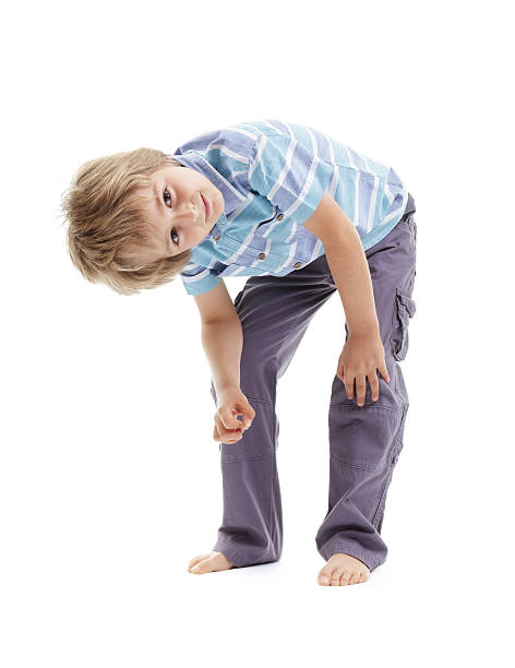 Curious and intrigued boy bending over Curious and intrigued boy bending over tilting head and looking up suspiciously bending stock pictures, royalty-free photos & images