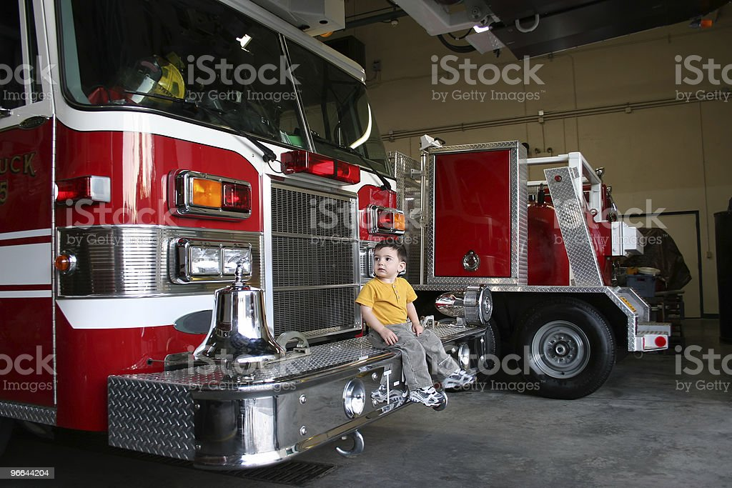 Curious Boy Sitting On A Fire Truck royalty-free stock photo