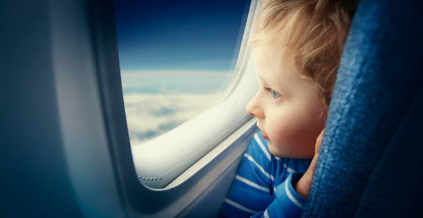 Curious boy watching sky from airplane window stock photo