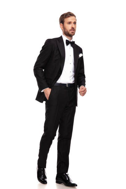 curious businessman in black suit looks to side while walking curious businessman in black suit looks to side while walking with hand in pocket, full length picture tuxedo stock pictures, royalty-free photos & images