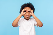 istock Curious child exploring world. Portrait of inquisitive nosy little curly boy looking through fingers shaped like binoculars 1203079046