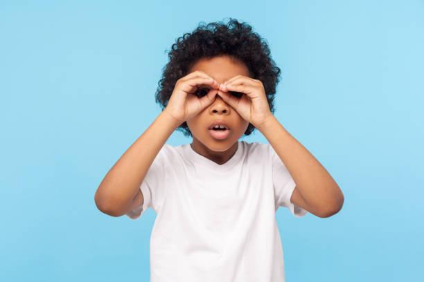 nyfiken barn utforska världen. porträtt av nyfikna nyfikna lilla lockig pojke tittar genom fingrar formade som kikare - investigating eye bildbanksfoton och bilder