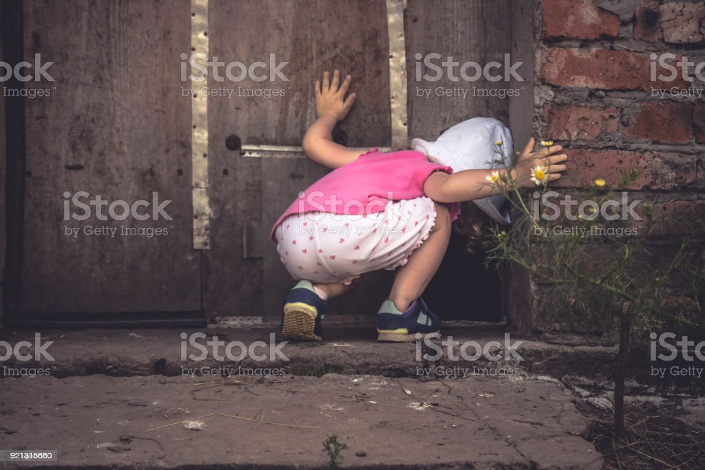 Curious child looking into dark hole in barn door in countryside shed concept curiosity stock photo