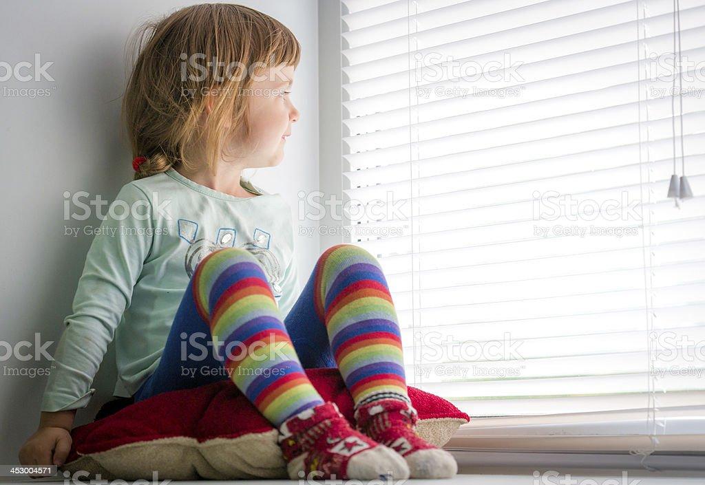 Любопытно ребенка выглядывает из окна стоковое фото